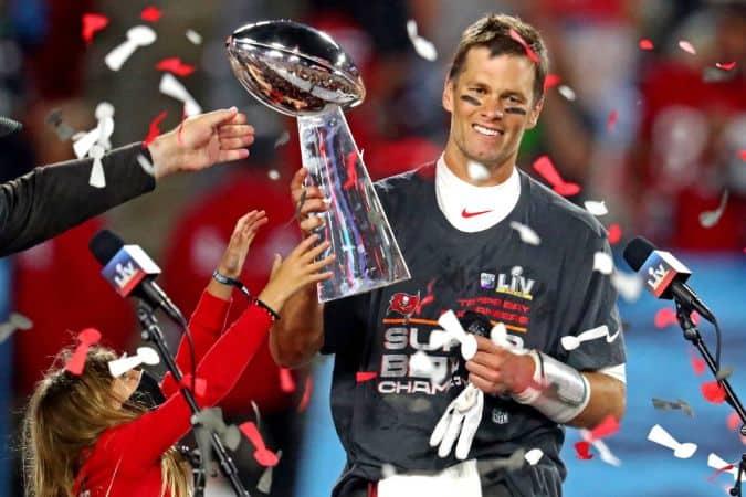 Tom Brady holding his Trophy