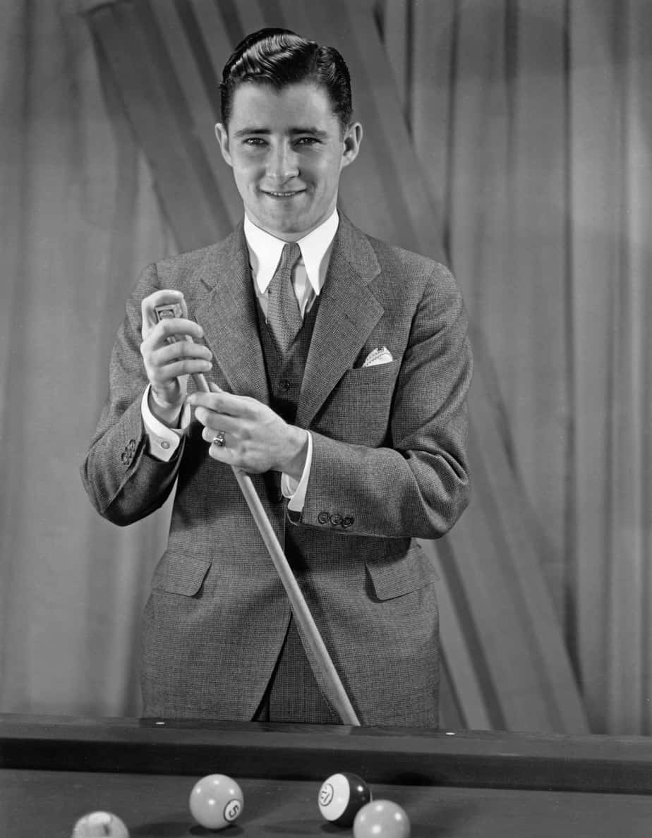 Willie Mosconi carrying a cue stick