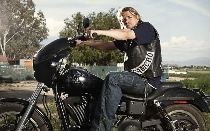 Charlie Hunnam is posing in a bike.
