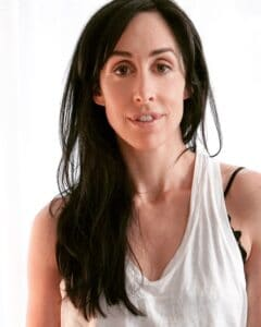 Catherine reitman in a white casual dress.