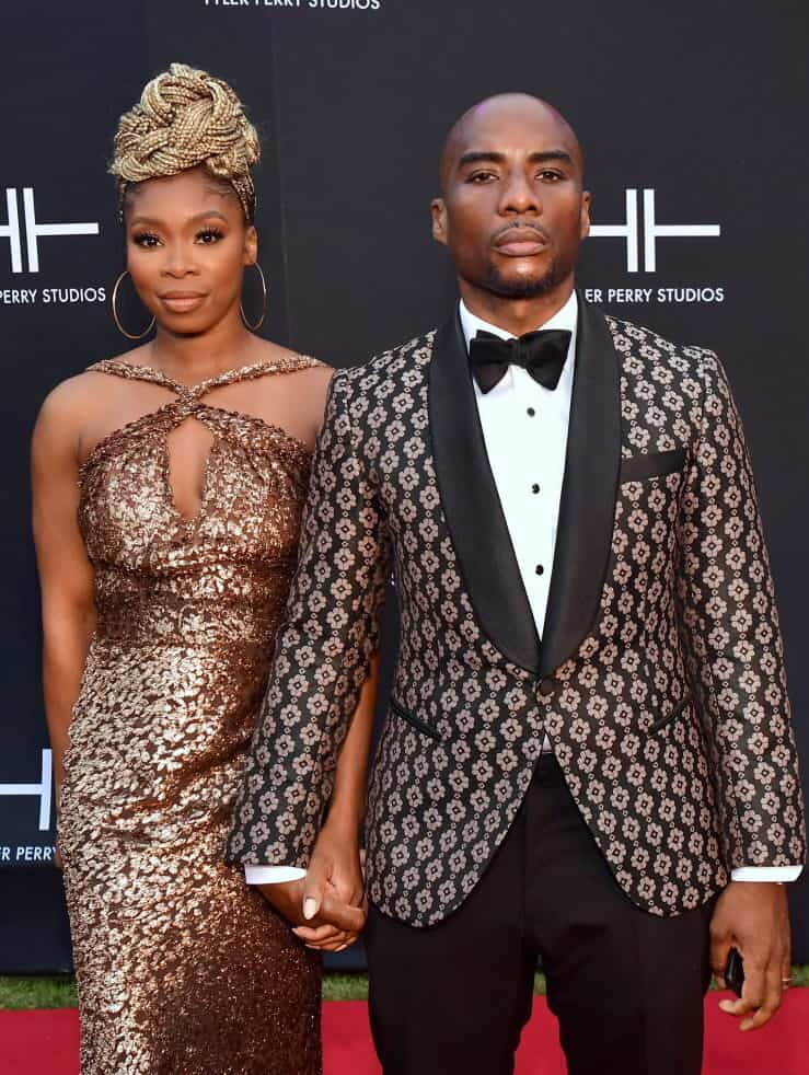 Charlamagne is taking pictures with his wife.