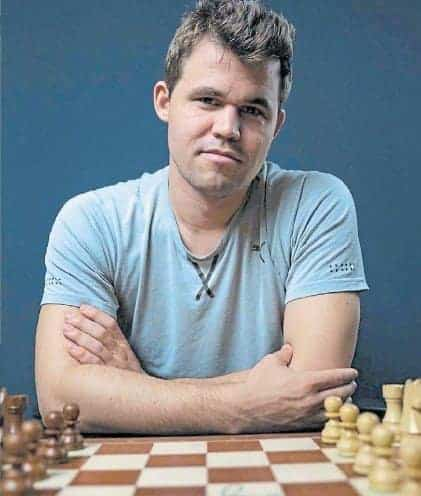 Smiling Magnus Carlsen in blue t-shirt